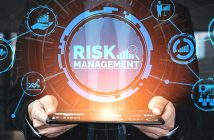 the word risk management in front of a man holding a tablet